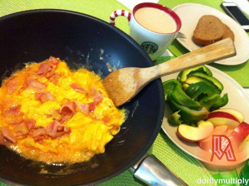 Scrambled egg with bacon, sliced green bell pepper and apples for breakfast